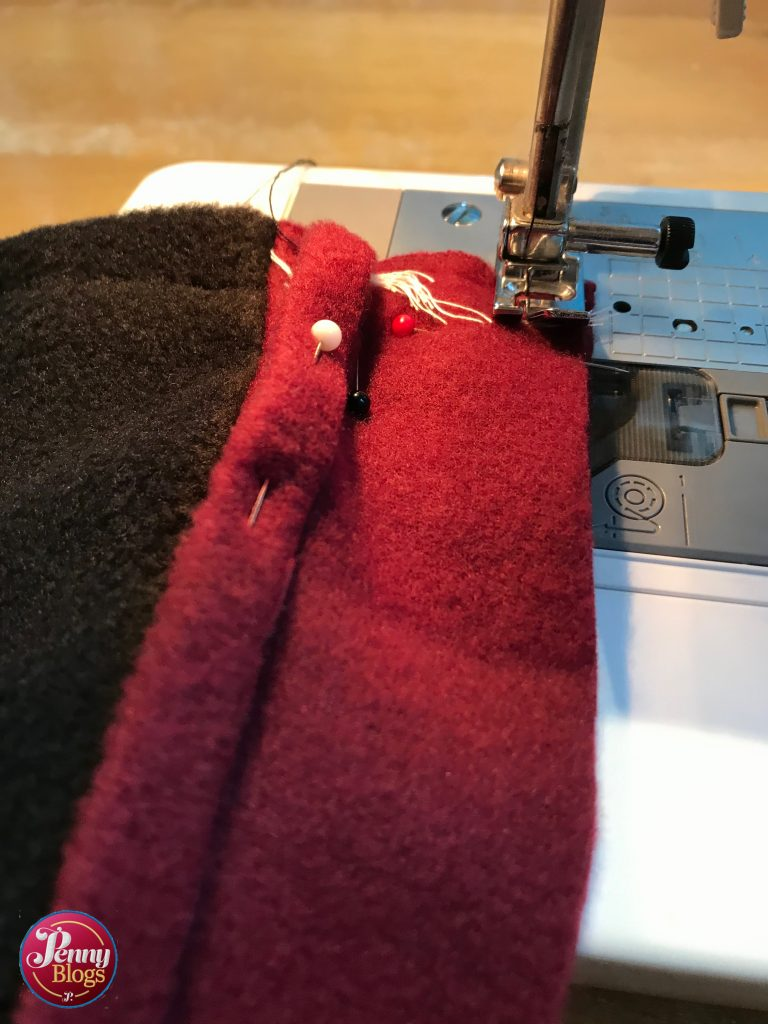A close up showing a piece of wine red fleece on the sewing machine