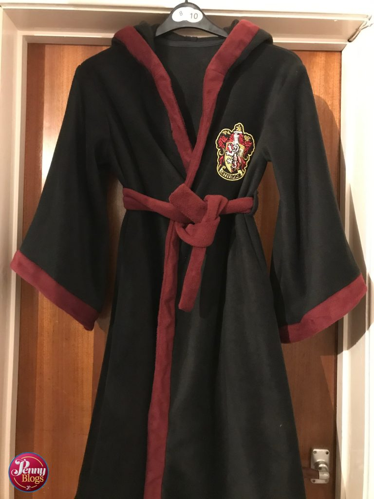 A completed Harry Potter Dressing Gown hanging on the back of a door. Mainly black in colour with a wine red trim and a Gryffindor badge on one side of the chest