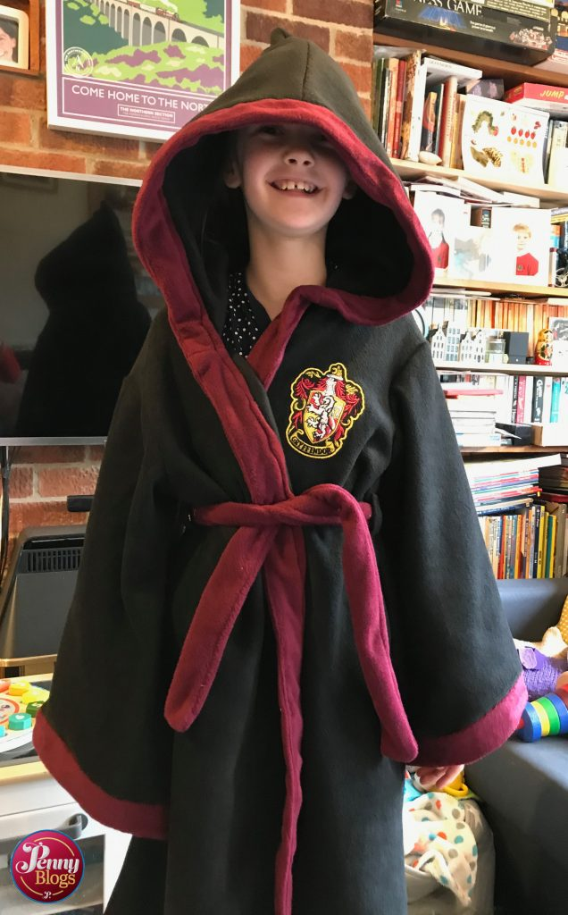 A ten yearly girl smiling whilst wearing a Harry Potter Dressing Gown with the hood up