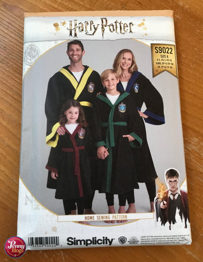 The packet of the Harry Potter dressing gown sewing pattern - simplicity pattern S9002 showing a family of four wearing dressing gowns, each one showing a different Hogwarts House colour on the trim