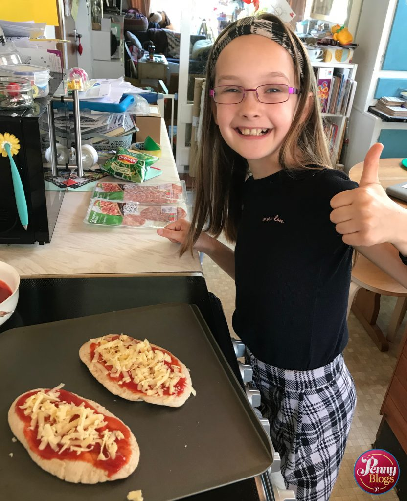 A girl showing a thumbs up next to two pitta bread pizzas ready to go into the oven