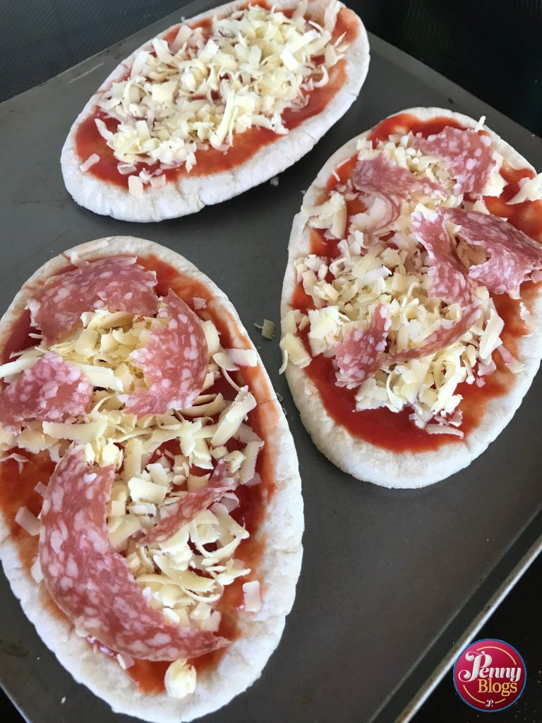 Three pitta bread pizzas ready for the oven